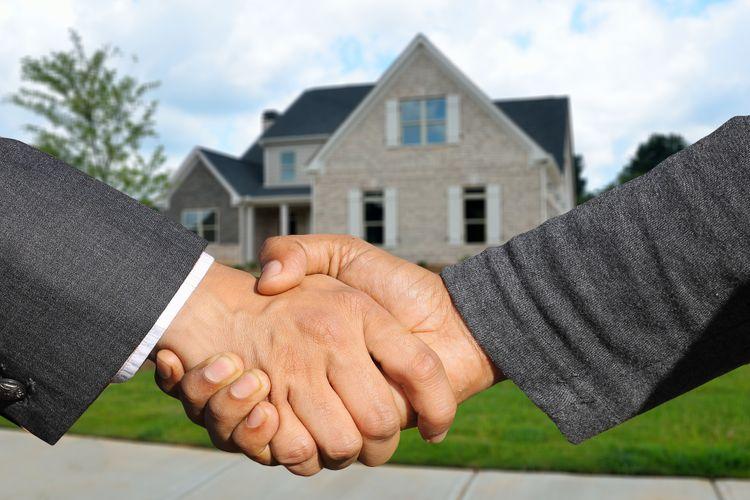 agente inmobiliario estrecha la mano de su cliente tras vender una vivienda